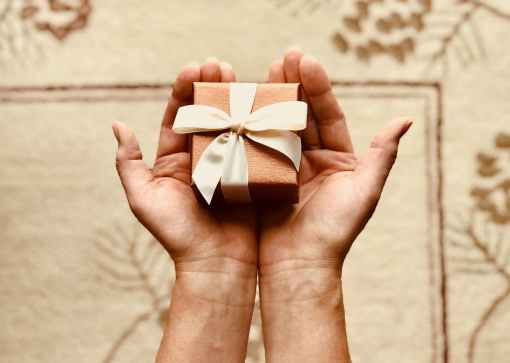 person s holds brown gift box